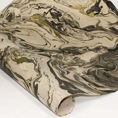 """Inspired from the veins of texture in granite and stone, this Marbled Lokta Paper takes earthy color to a whole new level. Intricate marbled patterns in glittering gold and black flow across each cream-colored sheet creating a one-of-a-kind design on each and every sheet.  Lokta Paper is a strong, durable and eco-friendly paper handmade from the fiber of the """"Nepal Paper Plant,"""" also called the Daphne Shrub or Lokta Bush. This paper features subtle fiber inclusions, adding handmade beauty…"""