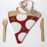 Simpatico bavaglino per neonato a forma di trancio di pizza margerita! Realizzato in spugna sottile di cotone color rosso, con dettagli in spugna di cotone bianca e pannolenci verde per le fogliol...