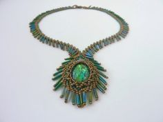 DIY Jewelry: FREE beading pattern for cabochon netted bezel framed with bugle fringes, resembling a peacock feather. Includes variation using fringe beads.