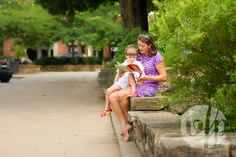 Downtown Fayetteville Square. Fayetteville Arkansas family photography by Whitney Flora Photography. Mother reads a book to her son.