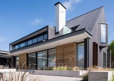 Dark-stained cedar gables contrast with knapped flint walls at this English countryside house