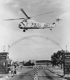 A Sikorsky SH-34G Seabat hovers over the main gate of NAS Ellyson Field, Pensacola, Florida, in 1964.