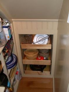 Slide out shelves of varying depth to maximize remaining space under the last few stairs