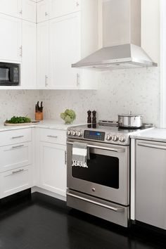 Calacatta marble countertops match the mosaic backsplash, and stainless steel appliances work well with the faucet finish and drawer pulls. Repeating the finishes eased the transition between the kitchen and the rest of the home.    Range: Profile, GE; hood: Zephyr