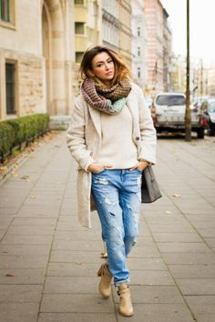 25 Ways to Style Baggy Jeans All Winter Long - cream winter coat + matching sweater worn with distressed baggy jeans + tan leather ankle boots