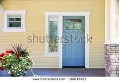 A front entrance of a home with a blue door, yellow siding, and a flowerpot in daytime.