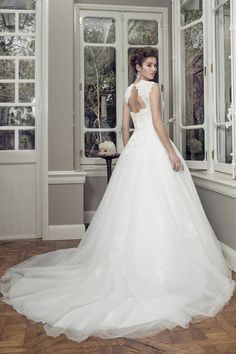 Tulle Ball gown wedding dress with sweetheart neckline and lace cap sleeves. Bodice featues satin waistband with jeweled detail. Keyhole back opening with button over zip closure. Chapel length train.