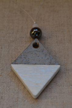 """Collier en béton """"Le Losange"""" - Collection """"Black & White"""" de Sésé'Dille.  Ce collier est composé d'un pendentif en béton en forme de losange peint en blanc, d'une perle d'Hématite, d'une perle de Swarovski blanche et d'un câble."""