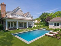 Simple yet Elegant Pool: Boxwoods anchor the base of the rear porch columns and the repeated use of the 2x2 thermal bluestone pavers set with lawn joints form a grid-like pattern. Tip: Having lawn on all sides of the pool and spa helps make the space feel more expansive. From HGTV.com's Garden Galleries