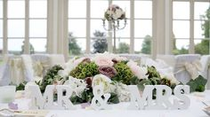 pretty wooden signs on the top table , to mark your first meal together as Mr and Mrs. flowers from Pollen flowers- styling from pollen4hire. sussex wedding venue- Buxted park hotel - the orangery