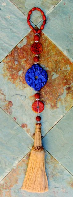 Hot orange and a vibrant blue combine in this UMANObead.  The hemp tassel shows how these colors create a pop against a neutral design palette.  Incidentally, the central hand carved medallion is a replica of an ancient Chinese plate that would be placed behind the  handle of a doors home.  The double dragons on the plate are there to protect the family from fire.  Hang this art on a wall and watch what it does.