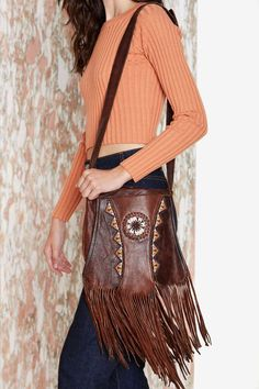 Pretty much the motherload of vintage western bags. It's leather with fringe detailing, beading detail, braiding design, shoulder strap, and...