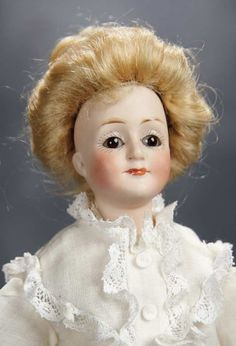 """Petite German Bisque Gibson Girl 10"""" (25 cm.) Bisque shoulderhead with uptilted face and elongated throat, brown glass inset eyes, painted lashes, feathered brows, closed mouth with wide center accent line, blonde mohair upswept wig over plaster pate, muslin body with stitch-jointing, bisque lower arms and legs, painted white stockings, black heeled ankle boots, antique costume. Condition: generally excellent. Marks: 6/0 172. Comments: Kestner, circa 1910, inspired by drawings by American…"""