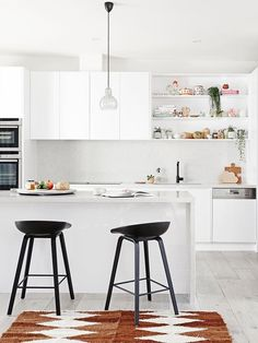 """This minimalist kitchen is brought to life with statement pendant lighting and pops of colour and greenery on the shelving. Take a tour of [this Scandi-style bungalow](http://www.homestolove.com.au/gallery-scandi-style-renovation-brings-bungalow-to-life-2053