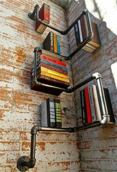 A perfectly arranged book shelf by industrial piping and rustic brick cemented wall.