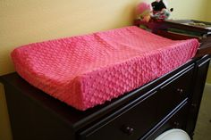 You'll want a contoured changing pad for your dresser or changing table because all of the changing pad covers are made for contoured pads.