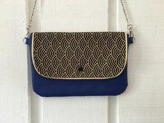 Pratique et léger ce petit sac pochette se porte en bandoulière ou à la main grâce à sa bandoulière amovible.   Pochette en similicuir bleu. Rabat en tissu japonais marine  - 18319698