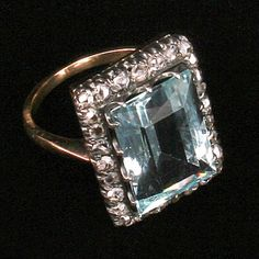 Great old Aquamarine and rose cut and mine cut Diamond ring. The band is not hallmarked, but tested 12K yellow gold. The top is all silver with many many prongs. The Aquamarine stone is a light sky blue/green. The stone measures 16mm X 10mm. There are 28 rose cut and mine cut Diamonds. Ring is size 7 1/2. Weight is 6.5grms. Condition is very good for age. I would date this ring at c1900.