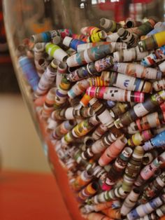 I love recycled magazine paper beads -- and here's a cool idea: displaying them in a glass vase instead of stringing them!