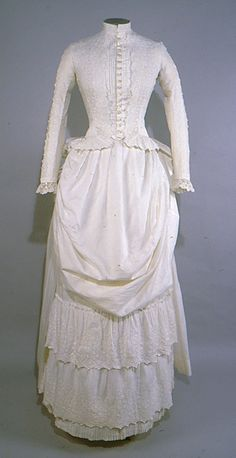 1886 Dress Culture: American Medium: cotton Dress; ivory cotton eyelet bodice and skirt; skirt has 2 layered eyelet ruffle in front and pleated hem. Bodice has a high round neckline with short standing collar. It opens down the center front and fastens with 17 round mother of pearl buttons. The center front opening is flanked by even, vertical tucks running from neckline to hem. Overlaid is a more elaborate layer of ivory cotton with white work and eyelet embroidered and a scalloped edge.