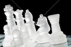 white chess pieces on chessboard - Close-up shot of white chess pieces on chessboard over dark background