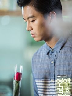tvN Marriage, Not Dating - Gong Gi Tae (Yeon Woo Jin) inspects a rosebud during his fake date with Joo Jang Mi.