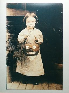 Antique photo of a little girl holding a Jack-O-Lantern candy basket for Trick-or-Treating.