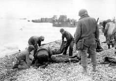 Sur une plage de galets à Omaha Beach, le 6 juin, des soldats US s'occupent de blessés. Tous ces hommes sont des Engineers, 5th ou 6th Engineer Special Brigade (voir le casque avec l'arc de cercle blanc et les chaussures : Jump Boots)
