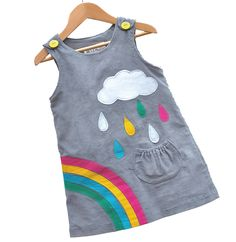 Wild Things Rainbow Dress Check out this adorable dress from our new brand, Wild Things Dresses! Brighten up those showery days with this beautiful cord rainbow & cloud applique pinafore. Silver cloud with pretty multi-coloured raindrops falling into a little pocket. Rainbow sweeps around one side giving a fantastic back view… Button fastening at shoulders. 2/3 lined in self fabric. Cord is a good weight for any season. 100% cotton, easy care.