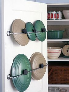 Storage solution for those pesky pot lids that never want to stay in place in the cupboard, mounted towel racks on the inside of the cupboard door.  Great idea!