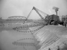 Aushub Baugrube Schleuse Feudenheim. Eimerkettenbagger beim Aushub der Baugrube der Schleuse Feudenheim, Abrammabtransport mit Feldbahnbetrieb, Riedbahn-Eisenbahnbrücke im Hintergrund. Aufnahme aus dem Jahr 1925.