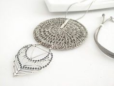 The necklace is made up of the gray suede strap with a locking washer to allow it to be adjusted to the most comfortable measure. The main piece that differentiates us, is crochet handmade with gray metallic thread of the recognized brand of tricot (ANCHOR), with silver beads bonded. To balance the