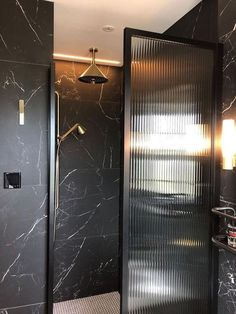 Fluted and Ribbed Glass Texture All black marble shower with single glass wall made from textured fluted glass with ribbed detail – interior design trends by the savvy heart.