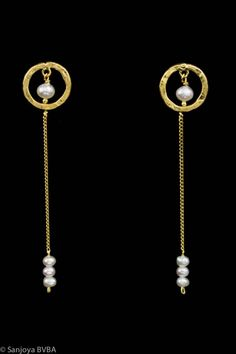 Beautiful and stylish long goldplated silver earrings by Sanjoya, with an open circle on the ear and a small pearl in the middle, attached thereto is a chain of three small freshwater pearls. A matching bracelet is also available. Greek design. For € 65,-. http://www.goldbergjuweliers.nl/en/sanjoya-long-goldplated-silver-earrings-with-pearl.html