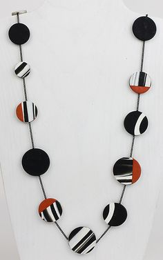 Maya Necklace by Klara Borbas. This striking necklace of solid and patterned polymer clay disks pairs with nearly everything thanks to its timeless palette of black and white, updated with dashes of vivid carmine. 38
