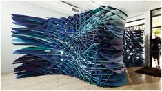 """""""Slipstream Installation"""": Translating a 2D digital line drawing into 3D, this installation at the Bridge Gallery in NYC captures the dynamics of turbulence in a colored gradient of (what looks to be) Foamcore board. While this is an art installation rather that architecture, the interlocking technique could be used effectively in (for instance) a retail store. 