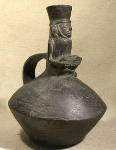 Chimu Fruit Vendor — Peru  1100 AD - 1400 AD  An unusual terracotta blackware Chimu vessel depicting a fruit vendor. Angular vessel with a wide strap handle on the back. On top is a seated figure holding an incised rectangular box containing three small spheres, representing fruit.