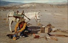 """Prospector's Camp Merle Porter A prospector prepares his breakfast of """"Flap Jacks"""" and coffee as his burro stands by. The burro will carry food and water for 10 to 12 days, along with the tools of the trade and the prospector's bed roll. As one drives along the modern western highways these old timers are often seen as they search for minerals."""