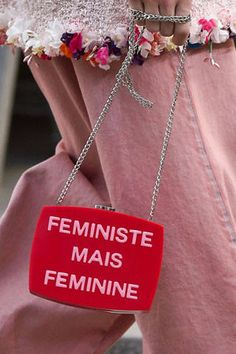 "Leave it to Chanel to pull off one of the most elaborate shows of the season. Models marched down a makeshift street in protest, all in the name of feminism. Our favorite accessory (other than the protest signs, of course) was this bright red bag with traditional Chanel chain, which reads ""Feministe Mais Feminine,"" translated in English as ""Feminist but Feminine.""    - ELLE.com"