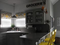 APRIL RUPPE this is for you!!! Grey and yellow kitchen, love the romans, bar stools, & sign....I would add a jar of lemons to countertop :-)
