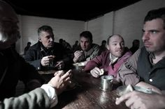 Group of men dressed as convicts eating and drinking together.