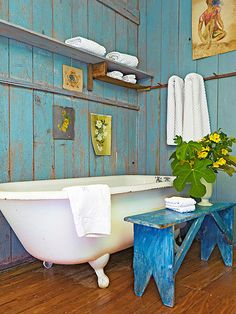Create a personality-plus rustic bathroom by layering surprising hues in unexpected ways. Turquoise-painted barn boards seemingly worn by the elements run from floor to ceiling to fashion weather-beaten borders. A painted bench contributes a cheery blue finish, while artwork, shelves, and a peg rack add good-looking utility to the bathroom walls.