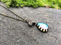 This Listing is for a Antique Bronze, milky blue Glass Opal necklace in a crown Teardrop Setting.@ artfire