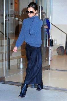 Victoria Beckham in a grey cable-knit turtleneck sweater + black flowy midi skirt + black ankle boots