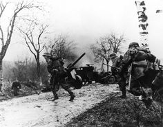 German soldiers cross a muddy road during the Battle of the Bulge, December 16, 1944