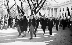 Photograph of Jacqueline Kennedy, accompanied by her brothers-in-law, Attorney General Robert F. Kennedy and Senator Edward Kennedy, walking from the White House as part of the funeral procession accompanying President Kennedy's casket to St. Matthew's Cathedral.