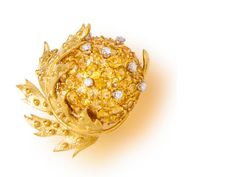 A yellow sapphire and diamond 'chestnut brooch', Jean Schlumberger, Tiffany & Co. pavé-set with yellow sapphires and circular-cut diamonds, enhanced by a textured gold leaf; signed Tiffany for Tiffany & Co. and Schlumberger; mounted in eighteen karat gold.