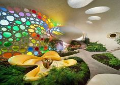 "an amazing interior shot of the ""rainbow glass"" underground home - with a unique concrete path and indoor plantlife"