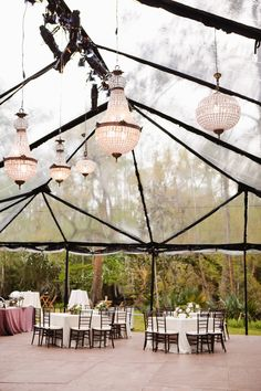 If you want an outdoor tent wedding, this is a great look that lets you enjoy the nature around you and gives you an elegant look! A Clear Tent with Chandeliers AND Lighting Design.  Looks great at night too!  Photo by Magnolia Pair