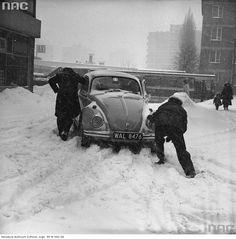 Mężczyźni pchający samochód Volkswagen Garbus.